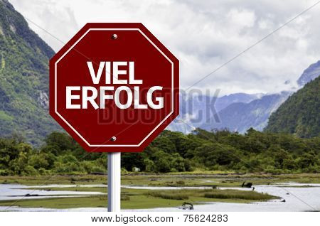 Much Success (In German) written on red road sign with landscape background