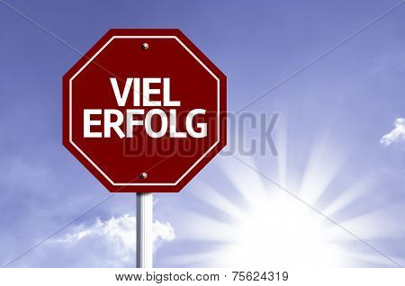 Much Success (In German) written on red road sign with a sky background