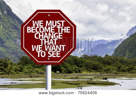We Must Become The Change That We Want to See written on red road sign with landscape background