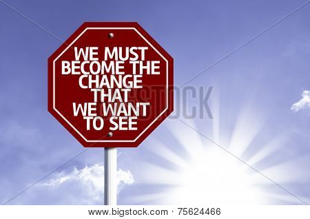 We Must Become The Change That We Want to See written on red road sign with a sky on background