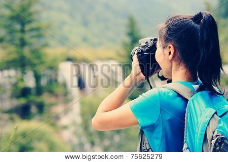 woman tourist/photographe taking photo with digital camera in jiuzhaigou national park,china