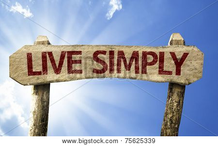 Live Simply wooden sign on a summer day