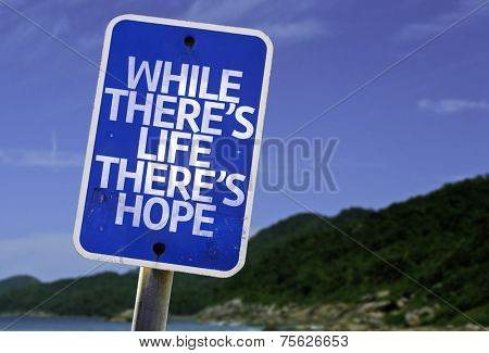 While There's Life There's Hope sign with a beach on background