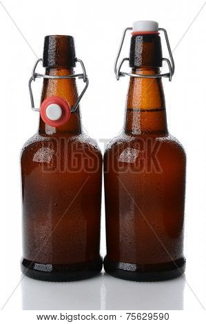Closeup of two cold swing top brown beer bottles covered with condensation, one bottle is open. Vertical format on white with reflection.
