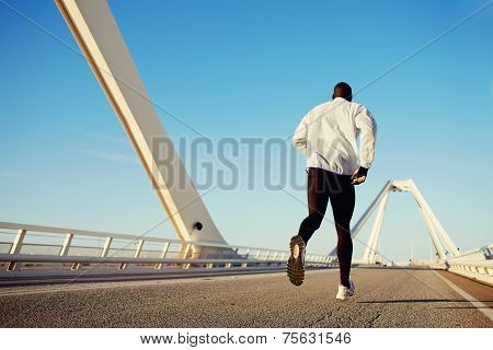 Attractive fit man running fast over beautiful road at sunset