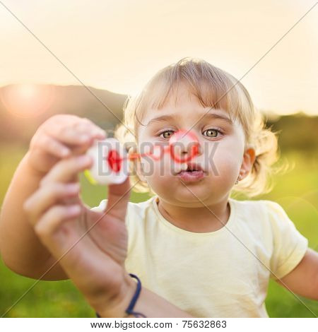 Little girl blowing bubbles in nature