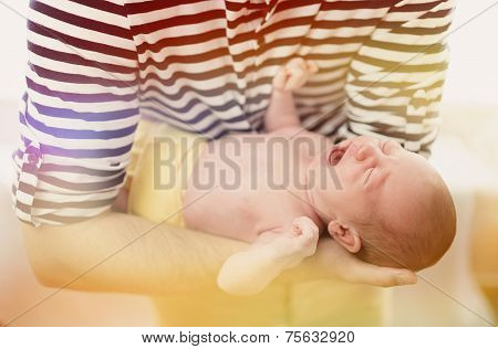 Father holding crying newborn baby girl