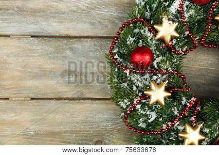 Green Christmas wreath with decorations on wooden background