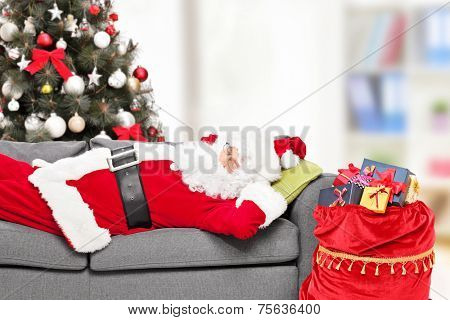 Santa Claus sleeping by a Christmas tree on a sofa at home with a bag of presents beside him