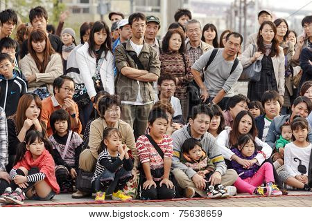 OSAKA, JAPAN, NOVEMBER 13, 2011: Japanese public crowd is watching a magician show performed at the aquarium square in Osaka, Japan