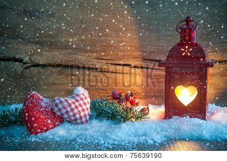 Christmas lantern with textile hearts and snow on vintage wooden background in night