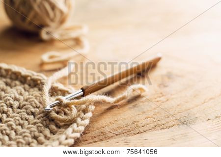 Crochet hook on wooden background