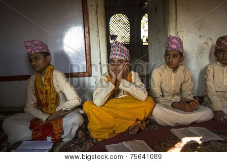 KATHMANDU, NEPAL - DEC 9, 2013: Unknown people during the reading of texts in Sanskrit at Jagadguru School. School established at 2013 to let preserve Hindu culture.