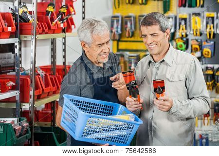 Senior salesman assisting customer in buying pliers at hardware store