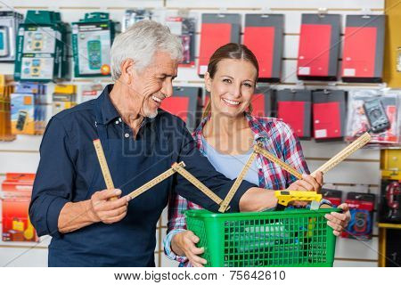Portrait of happy female customer with worker holding folding ruler in hardware shop