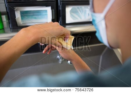 Rear view of female surgeon washing hands at washbasin in hospital