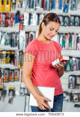 Beautiful mid adult woman holding digital tablet while examining product in hardware store