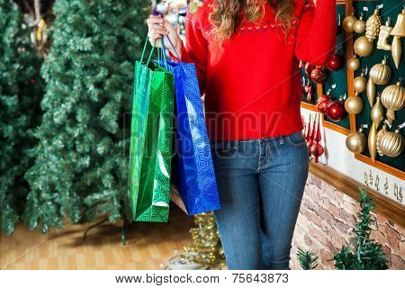 Midsection of young woman carrying shopping bags at Christmas store