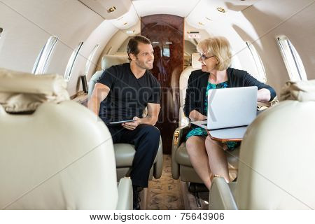 Business people with laptop and digital tablet discussing in private jet