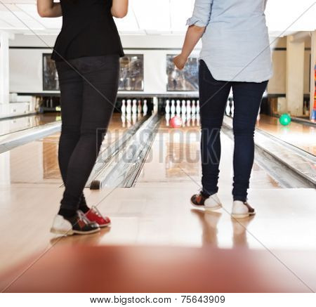 Low section of young female friends bowling in club
