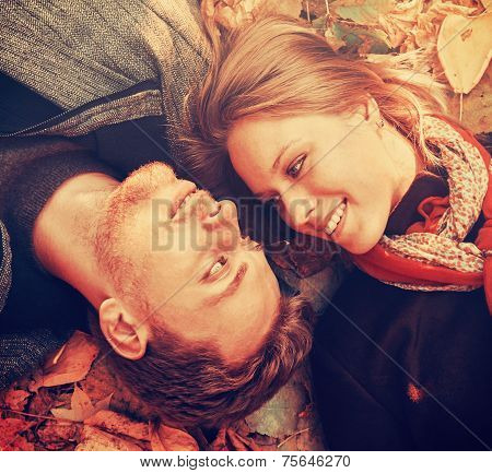 Happy Loving Couple Lying On Autumn Leaves , Close-up