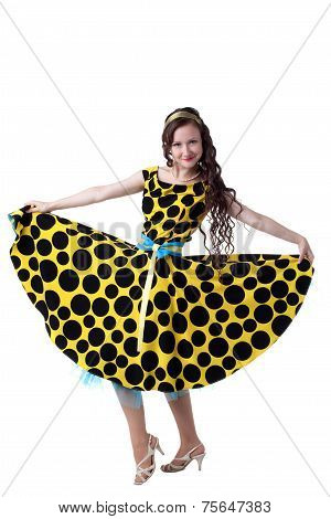Curly-haired fashionista posing in polka dot dress