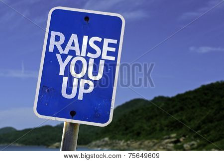 Raise You Up sign with a beach on background