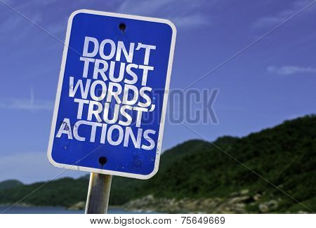 Don't Trust Words, Trust Actions sign with a beach on background