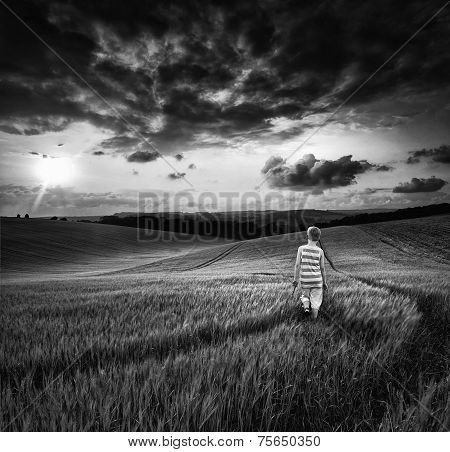 Concept Landscape Young Boy Walking Through Field At Sunset In Summer  Black And White