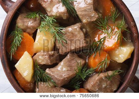 Beef Stew With Vegetables And Herbs In A Pot Macro Top View.