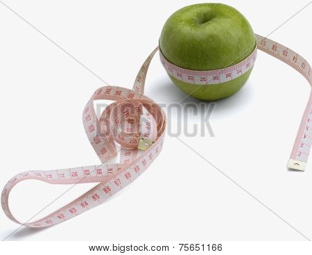 A green apple and a measurement tape , isolated on white background.