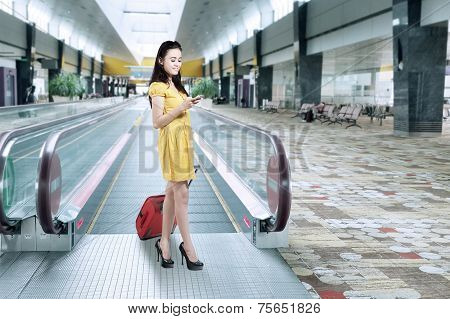 Girl With Luggage And Using Cellphone In Airport