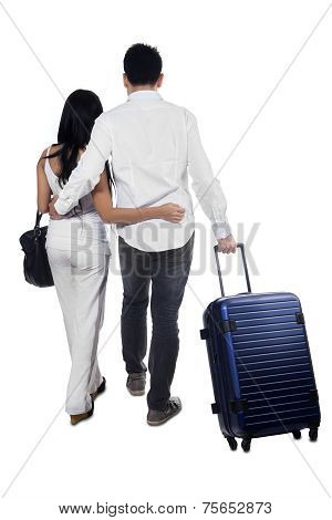Rear View Of Couple Pulling Luggage