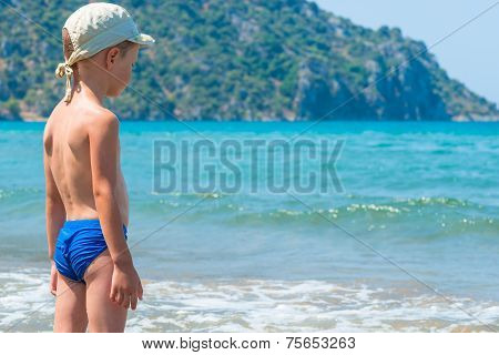 5 Years Old Boy In Swimming Trunks Is Looking At Waves