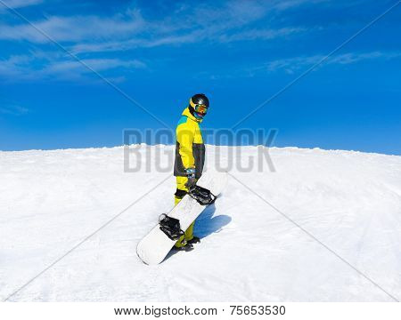 Snowboarder hold snowboard on top of hill