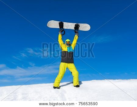 Snowboarder raised hands arms up hold snowboard on top of hill