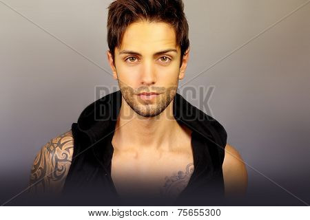 beautiful man with fashion appearance on a gray background