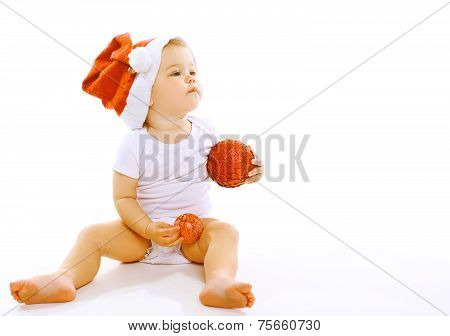 Christmas And People Concept - Little Baby In Winter Hat With Christmas Balls