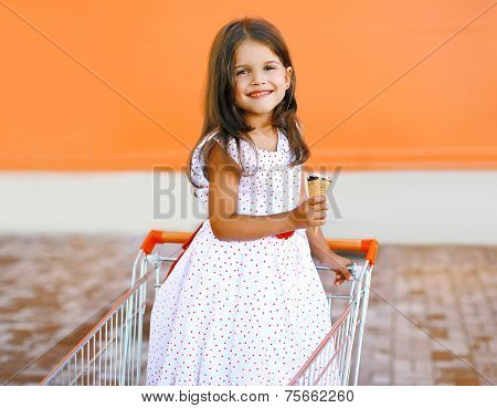 Happy Smiling Little Girl In Shopping Cart With Tasty Ice Cream Outdoors