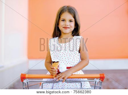 Portrait Happy Little Girl In Shopping Cart With Tasty Ice Cream Having Fun In The City