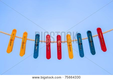Nine Plastic Clothespins Hanging On The Clothesline.