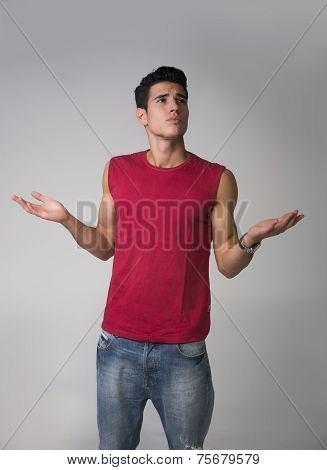 Handsome Unsure, Doubtful Young Man Shrugging With Arms Open