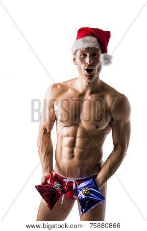 Muscular Young Man In A Speedo And Santa Claus Hat With 2 Christmas Gifts