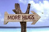 stock photo of sympathy  - More Hugs wooden sign with a beach on background - JPG