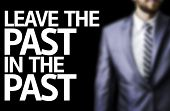 stock photo of past future  - Leave the Past in the Past written on a board with a business man on background - JPG