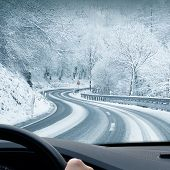 stock photo of curvy  - Curvy snowy country road leading through a mountain landscape - JPG