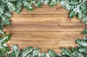 stock photo of fir  - Wood planks background framed with snow covered fir twigs a studio shot with nice bright lighting highly suitable for Christmas and winter season - JPG