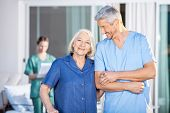 stock photo of male nurses  - Portrait of happy senior woman standing with male caretaker at nursing home yard - JPG