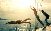 stock photo of bowing  - Silhouettes of young people diving from the bow of a boat - JPG