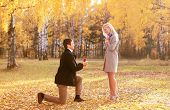 foto of propose  - Love couple relationship and engagement concept - man kneeling and proposing to a woman in the autumn park